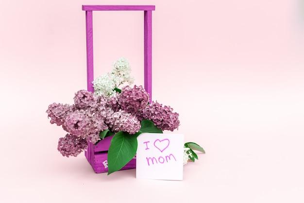 紫色のライラックと紫色の紙の背景にカードの美しい花束
