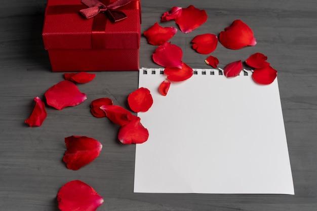 花束と赤いバラの花びらの横にあるテキストと赤いギフトボックスの紙の空のシート