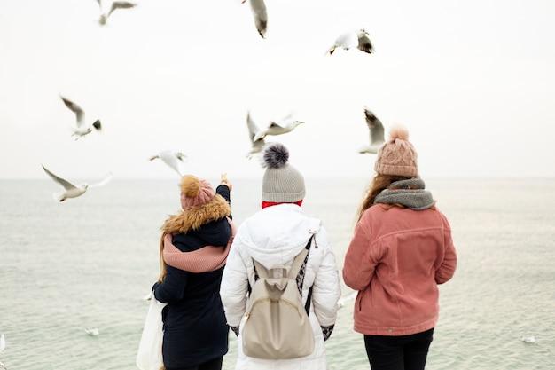 冬服を着ている人々のグループがドックの上に立っていて、彼らの手からカモメを食べています。