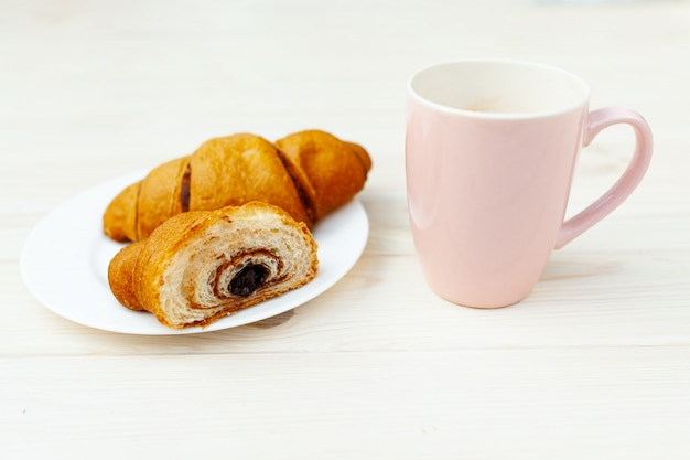 白い木製のテーブルにチョコレートと焼きたてのクロワッサン