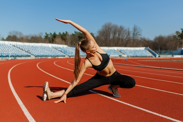 Молодой фитнес женщина бегун разминки перед запуском на треке. утренняя зарядка летом