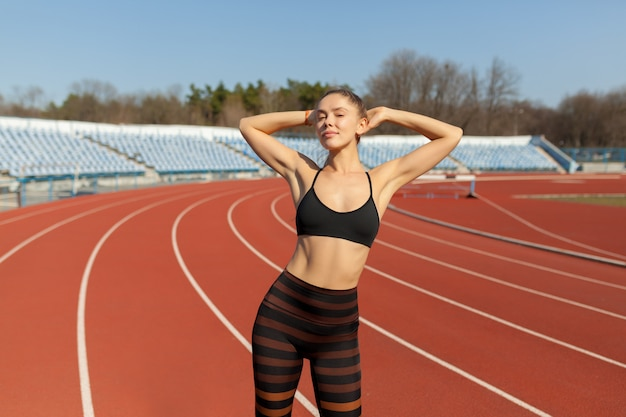 若いフィットネス女性ランナーがトラックで実行する前にウォームアップします。夏の朝の体操