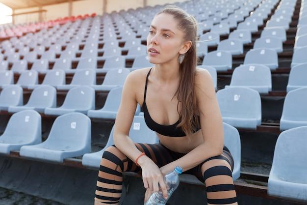Красивая кавказская девушка спортсмен держит в руках воду в пластиковой бутылке