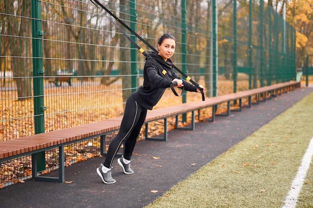 若い魅力的な女性は屋外フィットネスストラップでサスペンショントレーニングを行います