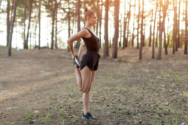 Молодая кавказская девушка на утре бежит в сосновом лесе.