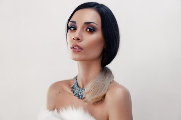 Портрет красивой молодой кавказской женщины одел искусственный мех