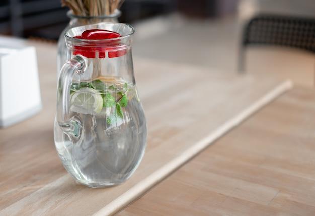 健康的な食べ物や飲み物。レモンとミントカフェの木製テーブルの上のガラスのマグカップに水します。さわやかな夏の飲み物。レモネード