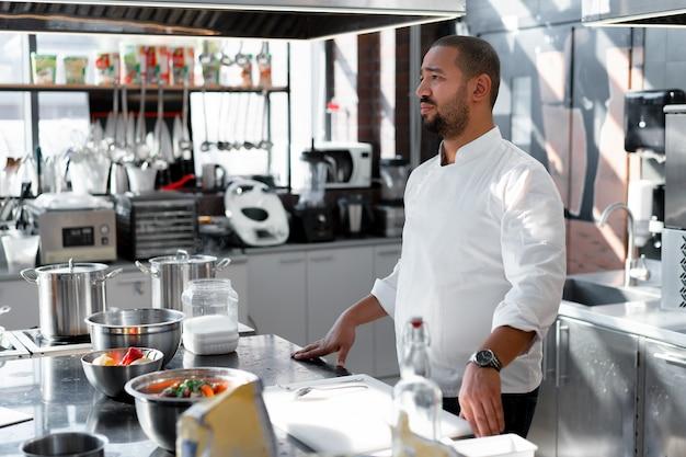 Шеф-повар проводит мастер-класс по кулинарии. на заднем плане стоит кухонная утварь, на столе перед ним овощи в мисках.