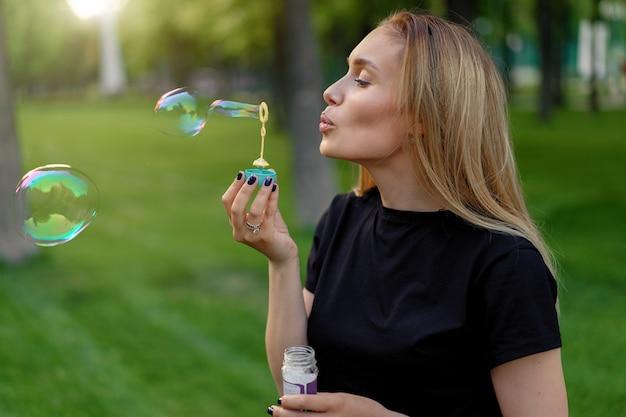 美しい少女は、夏の日当たりの良い公園でシャボン玉を膨らま