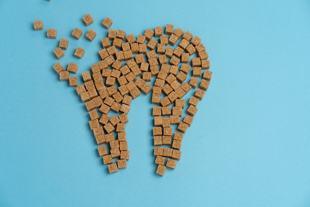 砂糖は歯のエナメル質を破壊します虫歯をリードしますホワイトシュガーキューブシェイプフォーム歯ブラウンシュガーカリエス青い背景ヘルスケアと医学口腔病学の概念甘い食べ物は歯を破壊します
