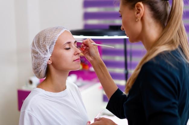 Кабинет косметолога клиент сидит на диване. косметолог наносит маркировку на брови. подготовка к процедуре перманентного макияжа бровей. свободное место. индустрия красоты