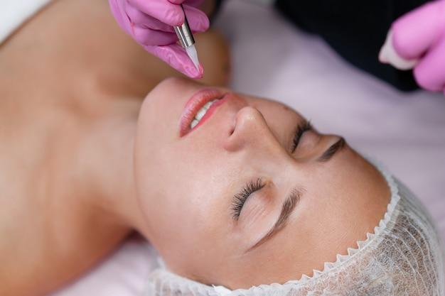 Косметологический кабинет клиента лежит на диване. косметолог наносит маркировку на губы. подготовка к процедуре перманентного макияжа губ. закройте индустрия красоты