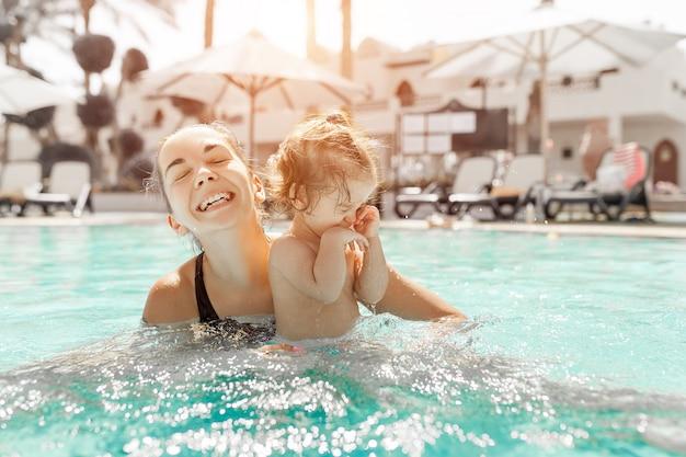 ママと幼い娘はオープンプールで遊んでいます。