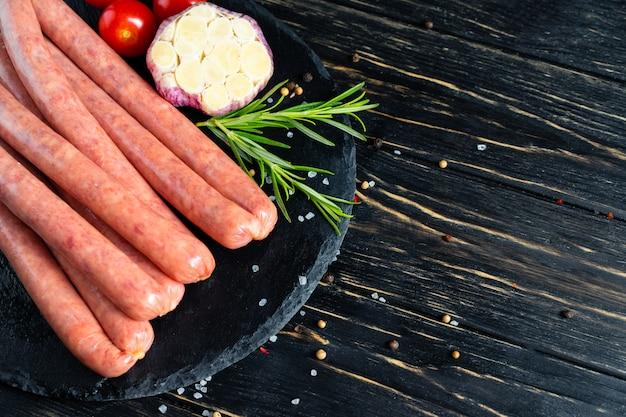 バーベキュー用のジューシーなソーセージは、ローズマリーとスパイス、コショウ、粗塩の石のまな板の上にあります