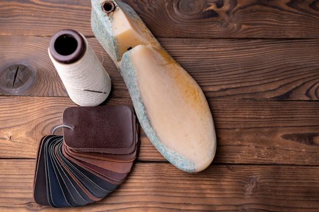 Образцы кожи для обуви и пластиковой обуви длятся на темном деревянном столе.