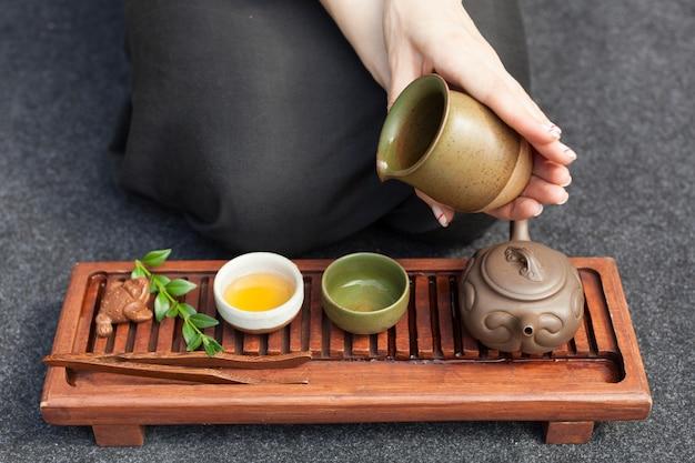 Традиционная чайная церемония крупным планом с женской рукой