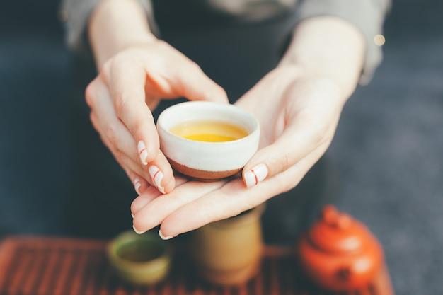 女性はヴィンテージのセラミックカップで熱いお茶を提供しています。