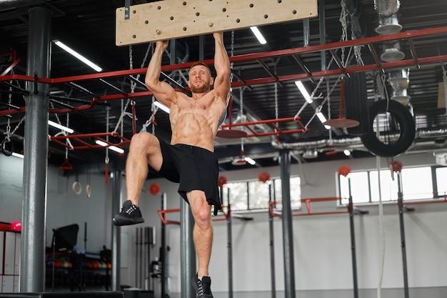 ペグボードジムアスリートトレーニング腕の強さを登る男