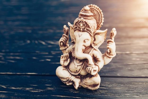 黒の背景にヒンズー教の神ガネーシャ。木製のテーブルの上の像