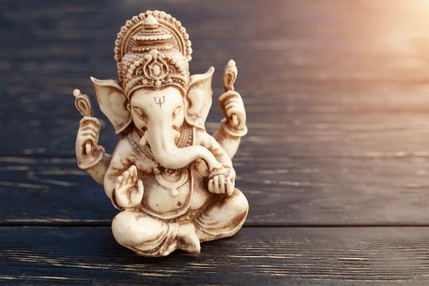 Индуистский бог ганеша на черном фоне. статуя на деревянном столе