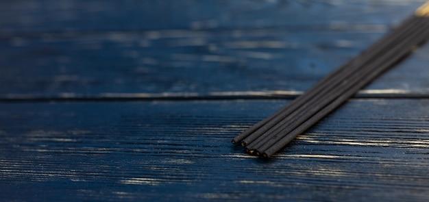 白檀は黒い木製のテーブルに付着します。アジアの伝統文化アロマテラピー