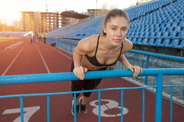 スタジアムで板の運動をしている魅力的な若い女性アスリート