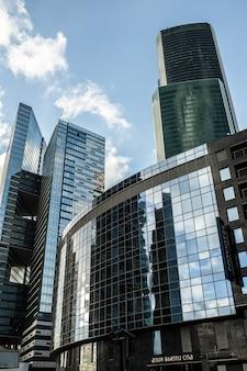 雲空と詳細青いガラスの建物の背景
