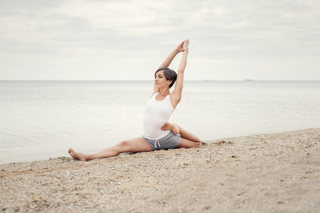 海の近くのビーチでヨガを練習する美しい少女。