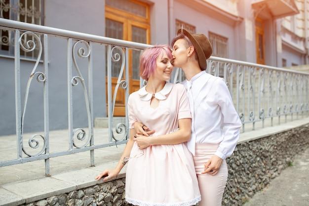 Две обнимающиеся девушки возле забора в городе