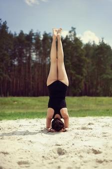 美しい少女は砂の上の森でヨガに取り組んでいます
