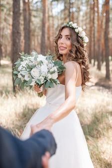 彼女のボーイフレンドの手を握って白いウェディングドレスに身を包んだ魅力的な若い女性