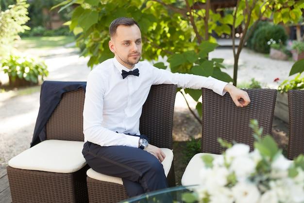 Красивый молодой деловой человек в белой рубашке и галстуке бабочки