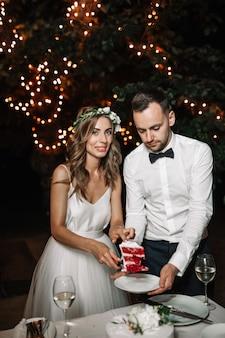 幸せな新郎新婦は前部の花輪の光の装飾でウェディングケーキをカットしました。