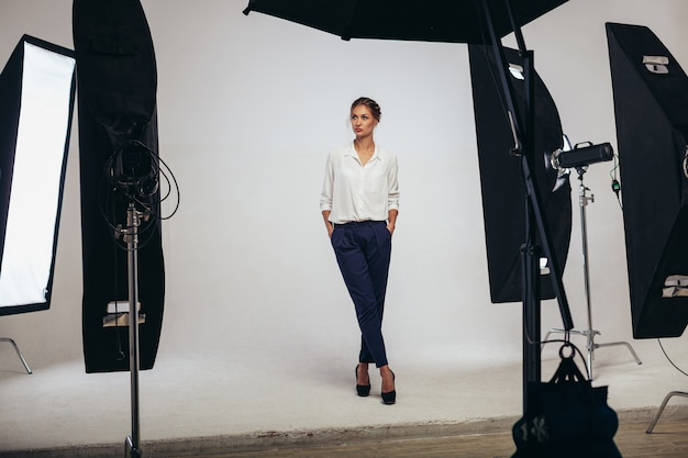 光のスタジオでポーズ美しいビジネス女性モデル