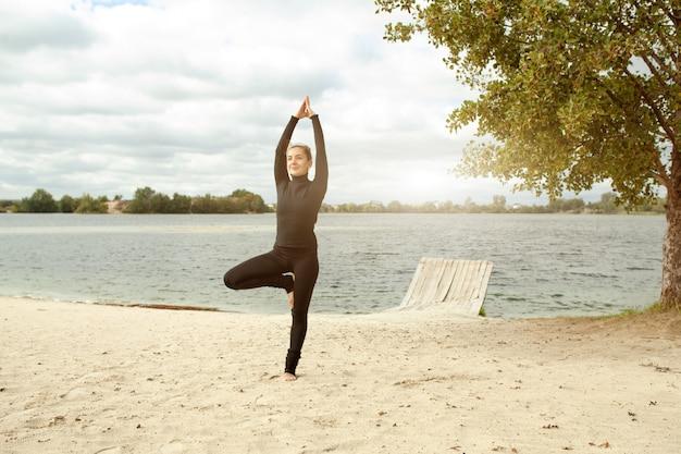 フィットネス、スポーツ、人とライフスタイルのコンセプト - ビーチでヨガの練習をする若い女性