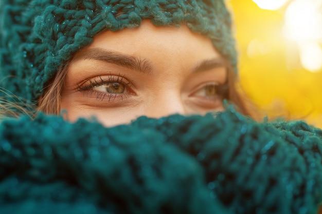 ニットスカーフを身に着けて笑顔の美しい自然の若い内気なブルネットの女性