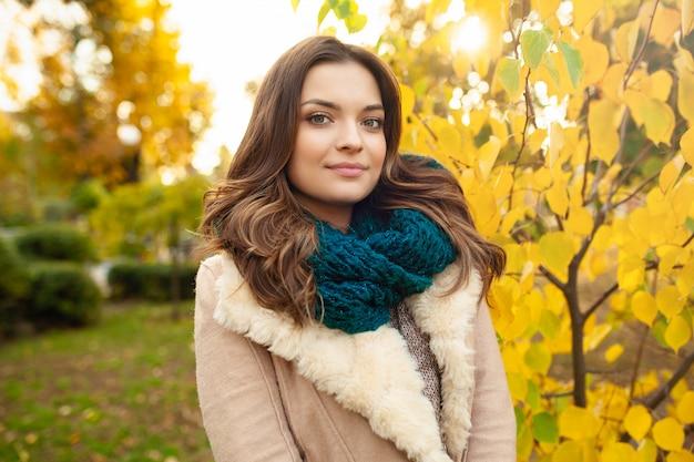 Красивая молодая девушка гуляет по осеннему парку на фоне ярко окрашенных листьев