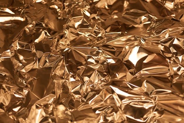Полный кадр из листа мятой золотой алюминиевой фольги