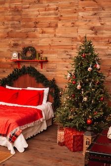 クリスマスのモミとベッド。ベッドとクリスマスツリーの部屋の新年インテリア。