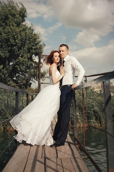結婚式の日の夕日に湖の近くの橋の上を歩く結婚式のカップル。恋に新郎新婦
