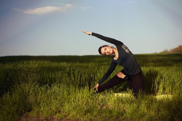 日光の下で小麦畑でヨガをやっている美しい若いブルネットの女性