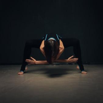 暗い織り目加工の壁に対してヨガの練習の女性