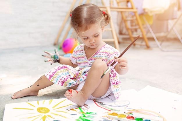 裏庭で絵画を楽しんでかわいい白人少女
