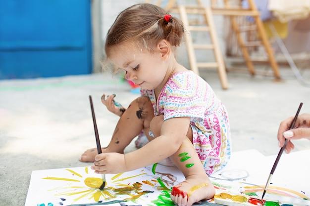 裏庭で紙、水彩画、アートブラシで絵を描く。