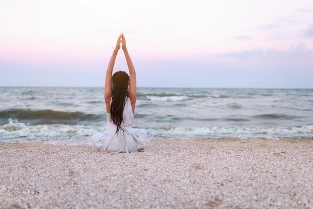 女性はヨガを練習し、ビーチの蓮華座で瞑想します。