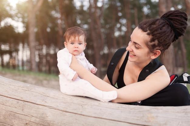 長いドレッドヘアの髪を持つ美しい笑顔若いブルネットの女性は、かわいい赤ちゃんを保持します。
