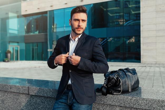 Красивый молодой бизнесмен с бородой и в деловом костюме