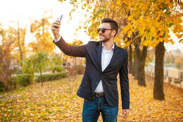Красивый молодой модный мужчина в стильном деловом костюме и солнцезащитных очках