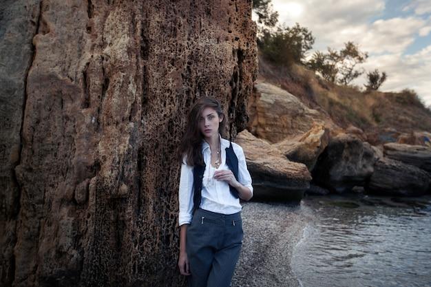 ビジネスの女性のスーツのベストと海のコストに大きな石の近くに立っている白いシャツ