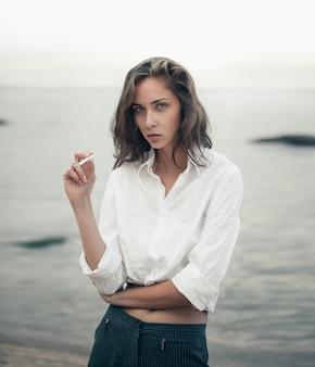 かわいい女性はビーチでタバコを吸う